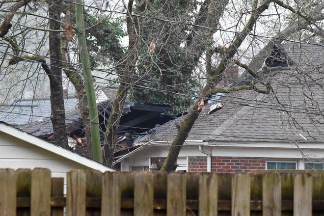 A single-engine plane hit the roof of a home in a Columbia neighborhood before slamming into the ground Wednesday morning. The home caught fire, but the woman inside got out safely. [MEG KINNARD/ASSOCIATED PRESS]