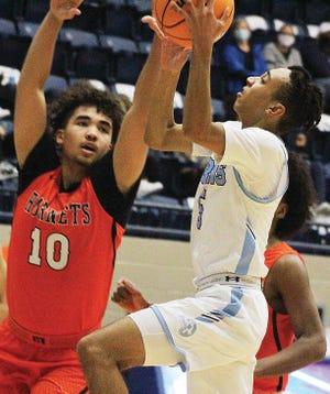 Bartlesville High School's Jordan Carter, right, powers toward the hoop while Tulsa Washington's Chase Carpenter defends during Tuesday's varsity boys basketball battle at the Bruin Fieldhouse.