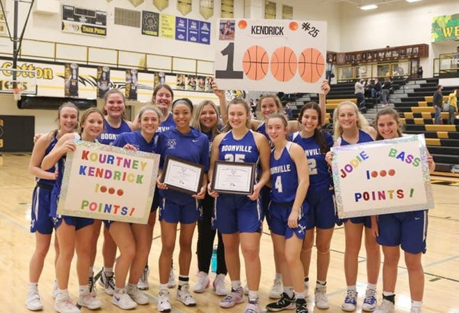 Members of the Boonville Lady Pirates basketball team honor seniors Jodie Bass and Kourtney Kendrick with posters after the duo surpassed the 1,000th point mark in their careers Tuesday night against the Smith-Cotton Lady Tigers.