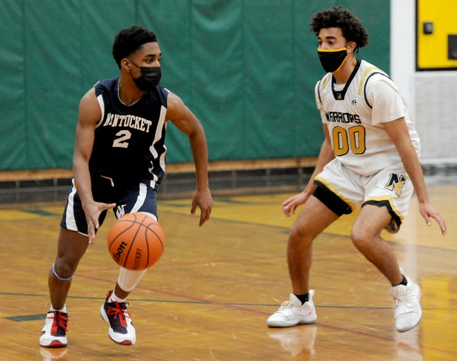 With Nauset's Michael Gray on defense, Nantucket's Makai Bodden takes the ball down court on Tuesday.  To see more photos, go to www.capecodtimes.com.