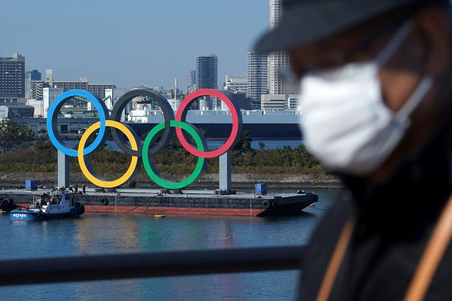 A man wearing a protective face mask walks with the Olympic rings in the background in the Odaiba section in Tokyo in this December 2020 photo. Opposition to the Tokyo Olympics is growing with calls for a cancellation as virus cases rise in Japan.