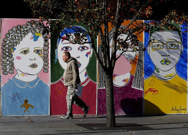 A man walks by a temporary mural by artist Charley Frances in front of Huntington Center on South High Street on Nov. 12.