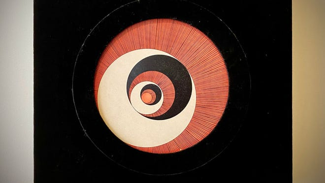 """This work, titled """"Rotorelief,"""" is by Marcel Duchamp, who was the pioneer of kinetic art, and is often referred to as the greatest artist of the 20th century. This piece uses a motor to rotate the circular section, creating an illusion of depth."""