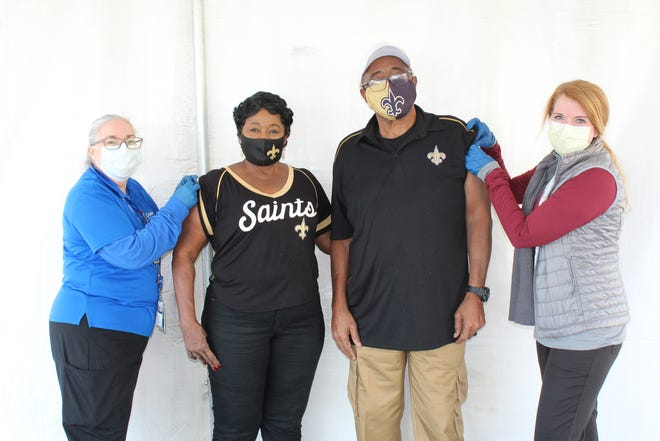 Johnnie and Bonnie McDowell of Thibodaux, loyal New Orleans Saints fans, have been going to the NFL team's games since the first one in 1967. They had to sit this year out due to the COVID-19 pandemic and related crowd restrictions. After receiving their COVID vaccine Wednesday at Ochsner St. Anne Hospital in Raceland, they say they are ready for the the Saints' next season. Delivering their vaccines are Angie Plaisance (left), registered nurse, and Dr. Jamie Huddleston. Ochsner St. Anne is among local hospitals and pharmacies offering COVID vaccines to people over 70.