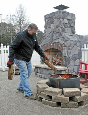 Dan Kinney of Lehman's in Kidron adds more wood to a smokeless fire pit, which will be used for a campfire cooking demonstration on Jan. 30 as part of June in January. A free-standing outdoor fireplace burns in the background.