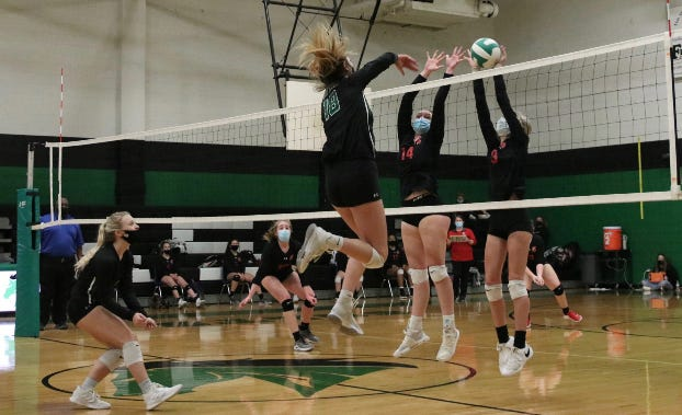 Central Davidson's Madison Tate (14) and Kyndall Norman (3) try to block a kill attempt by Kayli Cleaver of West Stanly in their first-round 2-A state playoff match on Tuesday. [Jennifer Barbee photo]