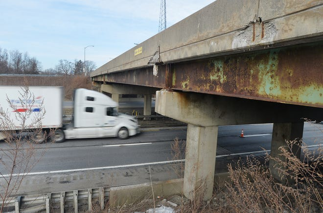 An eastbound truck passes under the damaged bridge that carries Route 215 over Interstate 90 on Wednesday in Springfield Township.