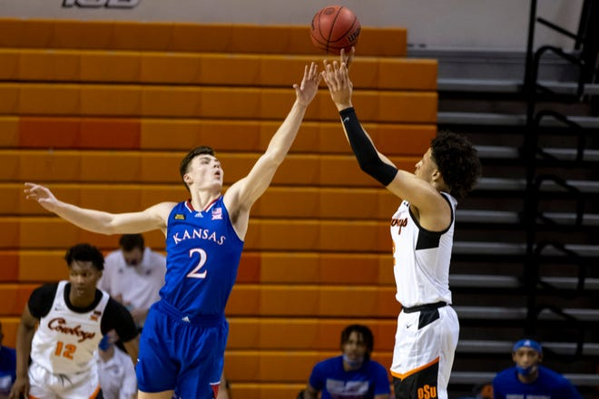 Oklahoma State's Cade Cunningham shoots over Kansas' Christian Braun during the first half of Tuesday's game in Stillwater, Okla. Oklahoma State claimed a 75-70 win.