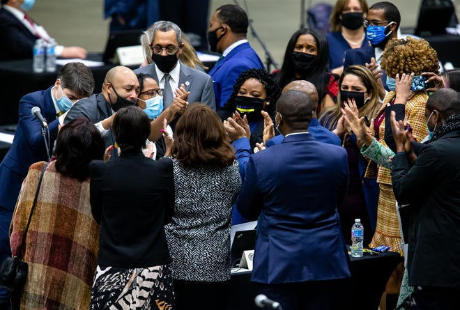 Rep. Justin Slaughter (left), D-Chicago, celebrates with lawmakers and staff after the criminal justice reform bill passes the Illinois House during the lame-duck session for the Illinois House of Representatives on Wednesday at the Bank of Springfield Center.