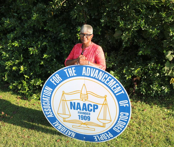 Kinston-Lenoir County NAACP president Barbara Sutton poses with the NAACP sign last year.