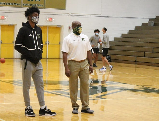 Kinston High basketball player Dontrez Styles (left) watches his team during warmups for the Jan. 12 game against West Craven. Styles, a University of North Carolina signee, was injured in the Vikings' season opener on Jan. 9.