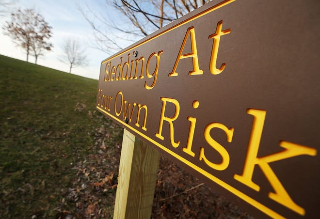 This is one of two sled riding signs that was recently posted at Hudson Springs Park by city staff. The signs were put up after city staff assessed the sledding risk after a child fell into a creek at the end of a ride last month. [Jeff Lange/Beacon Journal]
