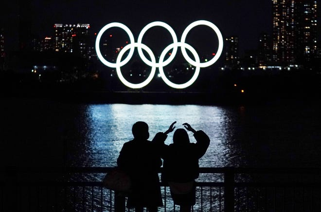 FILE - In this Dec. 1, 2020, file photo, a man and a woman look at the Olympic rings float in the water in the Odaiba section in Tokyo. Opposition to the Tokyo Olympics is growing with calls for a cancellation as virus cases rise in Japan.