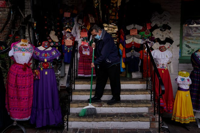 Victor Flores, 66, a third-generation owner of a gift shop, sweeps the steps of his store on Olvera Street in downtown Los Angeles on Dec. 16, 2020.  [AP File Photo/Jae C. Hong]