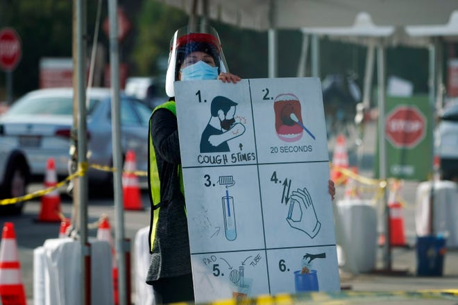 A worker gives instructions to motorists at a COVID-19 testing site in Los Angeles. [AP File Photo/Marcio Jose Sanchez]
