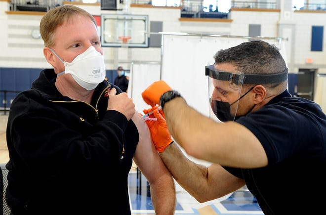 Milford Fire Chief Mark Nelson, left, receives the COVID-19 vaccine from Milford police Sgt. Robert Tusino, who is also the department's paramedic, at the Franklin High School gymnasium, Jan. 13, 2021. One hundred-and-eighty first responders from Franklin and surrounding towns were expected to receive the vaccine at the clinic.