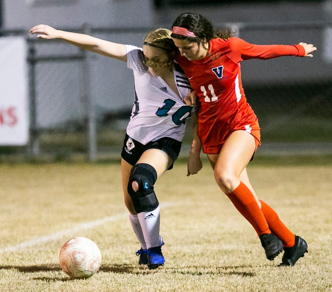West Port's Victoria Carter and Vanguard's Kaylie Saez battle for control of the ball in the second half. The Vanguard Knights defeated the West Port Wolf Pack 1-0 Tuesday night.