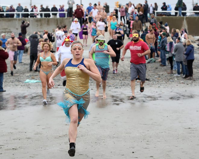 Melissa White, of Hull, sprints to the ocean to get ahead of the pack during the 25th Drowned Hugs fundraiser  for Wellspring on Saturday, Feb. 1, 2020.