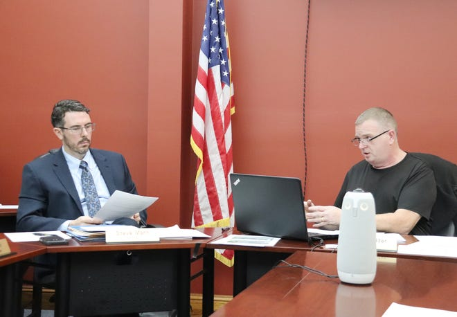 Chenoa Mayor Chris Wilder, right, discusses the proposed time-off measure that was approved at Tuesday's city council meeting. City Attorney Steve Mann listens as he goes over information that he helped draw up.
