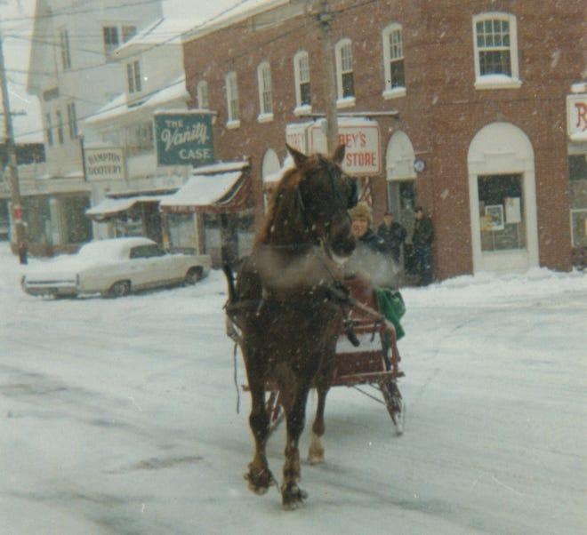 A horse drawn sleigh is seen in downtown Hampton.