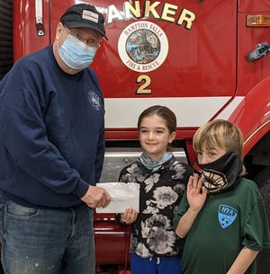 Longtime Hampton Fall EMT Hy Hubbard accepts a check from Dagny Crouse, 8 and Teddy Crouse, 7, the children of fellow department member Jackson Crouse. The children donated some of the profits from their summer roadside stand.