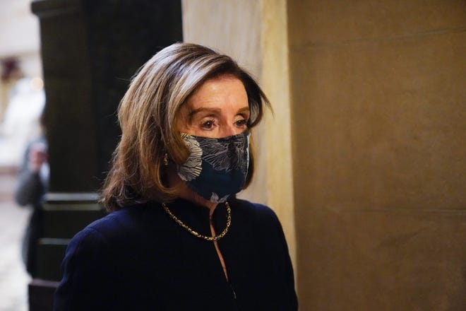Speaker of the House Nancy Pelosi of Calif., returns to her leadership office from the House chamber at the Capitol in Washington on Wednesday, as the U.S. House of Representatives pursues an article of impeachment against President Donald Trump for his role in inciting an angry mob to storm the Capitol on Jan. 6.