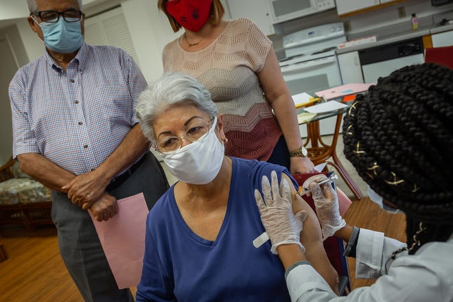 Patria Carlin, seated, is inoculated with Pfizer-made COVID-19 vaccine at AHEPA 18 Senior Apartments in West Palm Beach, Fla., on Wednesday, January 13, 2021.