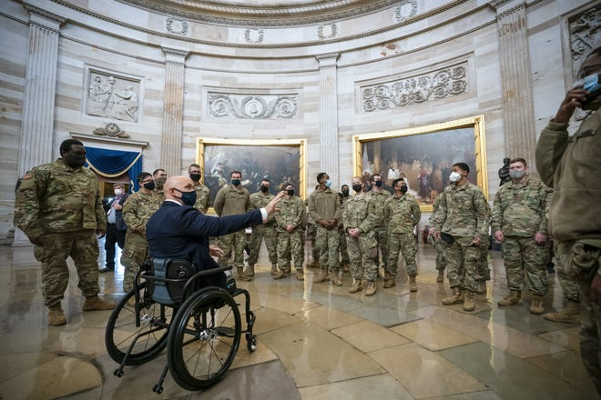 Rep. Brian Mast, R-Fla., left, visits with National Guard troops who are helping with security at the Capitol Rotunda in Washington, on Jan 13.