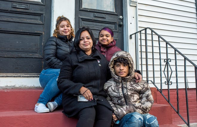 Glendaliz Colón, elected to the Central Falls City Council in November after recovering from COVID-19, sits on the front steps of her Dexter Street home with children Andrializ Rosario, 18; Ysabella Rosario 11; and Andres Rosario, 13.