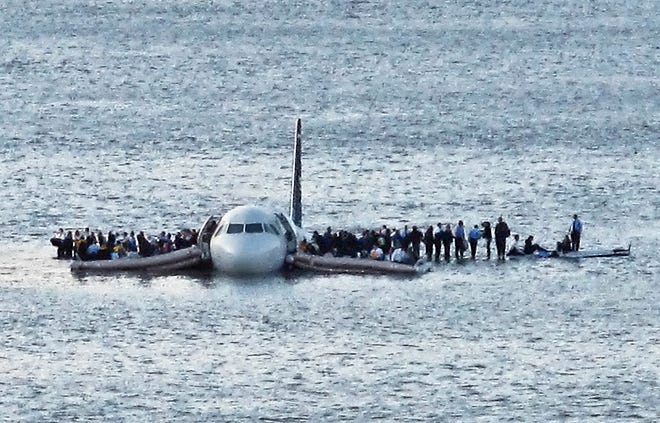 Airline passengers wait to be rescued on the wings of a US Airways Airbus 320 jetliner that safely ditched in the frigid waters of the Hudson River in New York on Jan. 15, 2009, after a flock of birds knocked out both its engines.