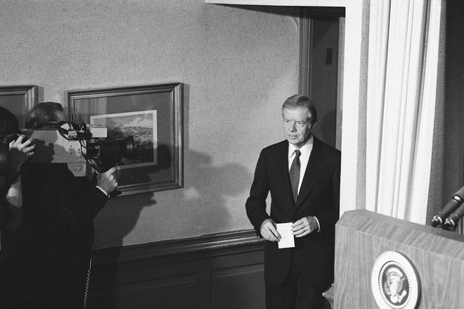 President Carter prepares to step up to the podium in the briefing room of the White House on Jan. 19, 1981, to announce a settlement has been reached that should allow the release of the American hostages held in Iran. Carter said he would have more to say when the hostages actually were released.