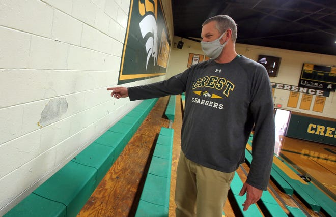 Crest Athletic Director Jeff Melton shows where repairs need to be made to the Crest High School gym on Wednesday.