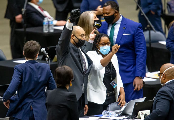 Illinois State Rep. Justin Slaughter, D-Chicago, holds up his fist while wearing a black glove after the criminal justice reform bill passes the Illinois House during the lame-duck session for the Illinois House of Representatives held at the Bank of Springfield Center, Wednesday, January 13, 2021, in Springfield, Ill. [Justin L. Fowler/The State Journal-Register]