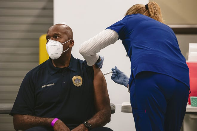 Melanie Willoughby, Dir. of Health Management at St. Joseph's/Candler, administers the COVID-19 vaccine to Savannah Police Chief Roy Minter Wednesday afternoon at the Savannah Police Training Center. (Richard Burkhart/Savannah Morning News)