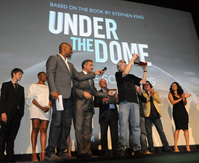 """Wilmington Mayor Bill Saffo reads a proclamation and presents author Stephen King with a key to the city as Thalian Hall hosts a screening of CBS' Wilmington-shot """"Under the Dome"""" on June 20, 2013."""