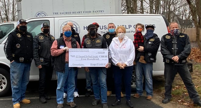 """Members of the Wings of Gold Motorcycle Club Plymouth Chapter recently presented the Sacred Heart Food Pantry with a donation check for $500. Seen here, from left, front, David Cunningham, Director of the Sacred Heart Food Pantry; Mikeal """"Pepé"""" Benoit, President Wings of Gold; and Arlyn White of the Sacred Heart Food Pantry; back, Ezzy, Chopper, Pack, Sparky, Junior, B-lo, and Stache."""