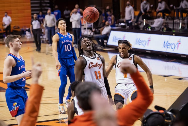 Kansas basketball's Christian Braun, left, and Tristan Enaruna, back, look on as Oklahoma State's Isaac Likekele, middle, and Rondel Walker celebrate a basket during the second half of Tuesday's game at Gallagher-Iba Arena in Stillwater, Okla. The No. 6-ranked Jayhawks lost 75-70.
