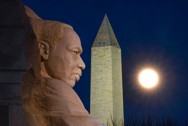 A rising full moon passes behind the Martin Luther King Memorial and the Washington Monument on Dec. 29 in Washington