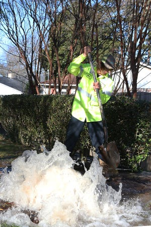 Mark Jones with the Fort Smith Water Department's Line Maintenance works to divert water to a nearby ditch from a break in a 6-inch water line, Tuesday, Jan. 12, at 3300 S. 27th St.