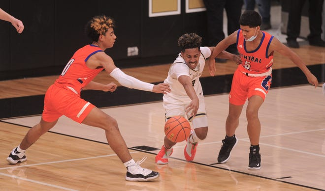 Abilene High's Jalen McGee, center, drives between San Angelo Central's Branden Campbell, left, and Mathew Cooper in the second half. AHS beat the Bobcats 76-52 in the District 2-6A game Tuesday at Eagle Gym.