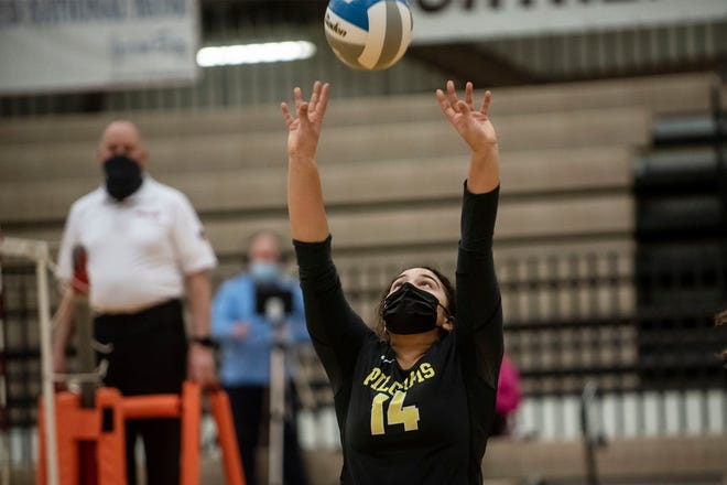 Lansing Christian sophomore Madelynn Rottman (14) sets the ball on Tuesday, Jan. 12, 2021 at Portage Northern High School in Portage, Mich. St. Philip defeated Lansing Christian 3-2.