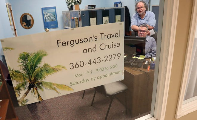 Arthur Ferguson and Paul Gaudette are seen through the front window as they work at their Ferguson's Travel and Cruise office in Port Orchard on Tuesday.