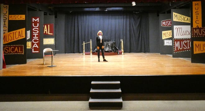 """Cindy Light, Bucyrus Little Theatre board president, stands on the theater's stage Wednesday afternoon. Since production of """"Musical of Musicals (the Musical)"""" halted after its first weekend in March, the stage has been mostly empty."""