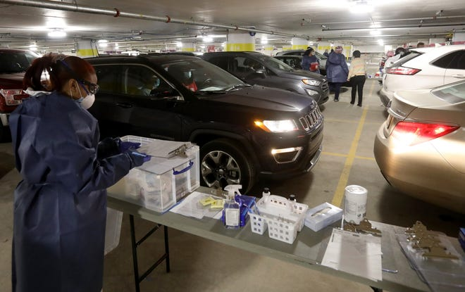 Several lines of cars wait for their turn to get the Covid-19 vaccine as nurses and others at table have all the necessary paperwork and medical supplies for the vaccine.