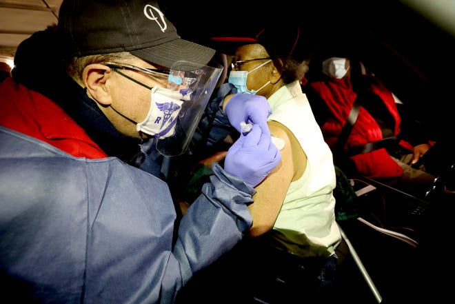 Jeffrey Sure, 60, a RN from Farmington, Michigan gives the first dose of the Covid-19 vaccine to Thelma Rudolph, 87 of Detroit.