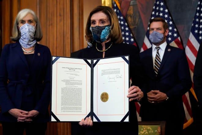 Ketua DPR Nancy Pelosi dari California, menampilkan artikel pemakzulan yang ditandatangani terhadap Presiden Donald Trump dalam upacara mengasyikkan sebelum dikirim ke Senat untuk diadili di Capitol Hill, di Washington, Rabu, 13 Januari 2021.