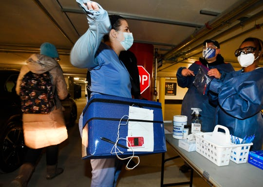 Meghan Boomhower with a cooler containing doses of vaccine at a COVID-19 vaccination drive-thru center at the TCF Center in Detroit on Wednesday.