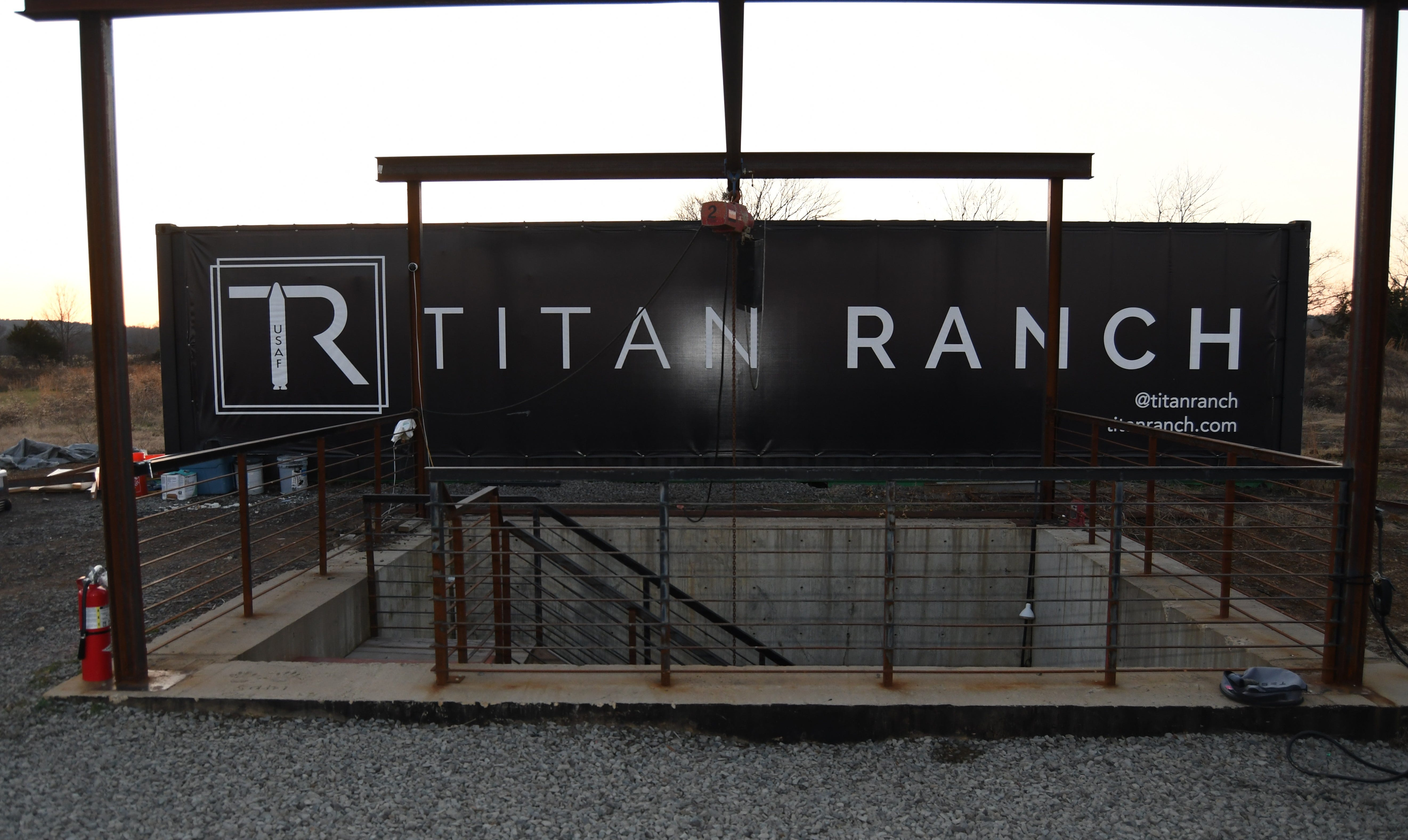 The entrance staircase to the Titan Ranch underground facility can be seen behind this sign.