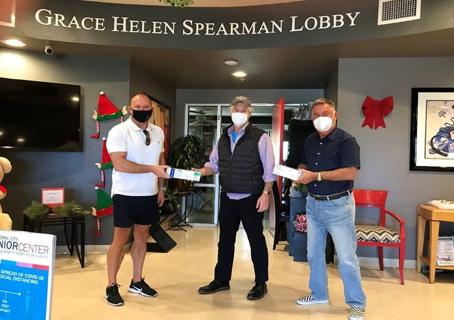 Jim Scheibel and Bertil Lindblad from the United Nations Association of the Coachella Valley present Geoff Corbin, executive director of the Cathedral City Senior Center (center), with packages of sterile masks and gloves.