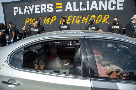 Local residents sit in their car while the Players Alliance and Pull Up Neighbor distributed fresh produce and athletic goods during a pop-up food pantry outside Pilgrim Rest Baptist Church in Phoenix on Jan. 13, 2021.